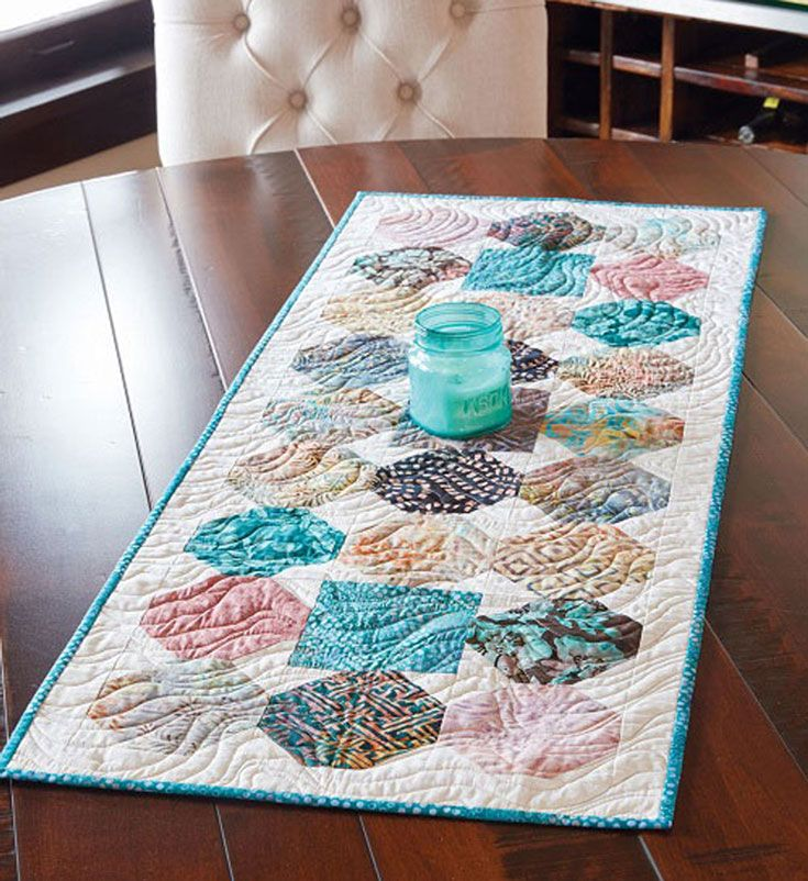 Use nature-inspired, colored batiks in pre-cut 5″ squares to replicate this beautiful table quilt pattern. Table runners are fitting décor for kitchens, dining rooms and living spaces and act as great conversation pieces when entertaining guests. This light and airy table quilt pattern offers a sense of calm – the perfect atmosphere for any home.