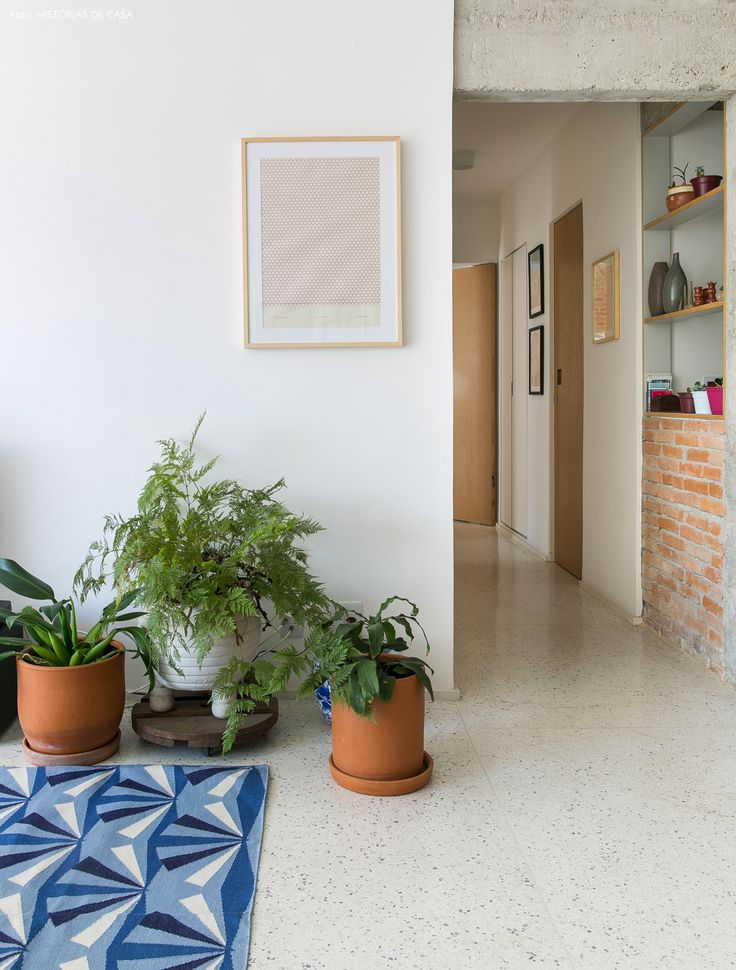 corredor de uma sala de estar com parede de tijolinho e piso de granilite branco - matéria em parceria com a https://boobam.com.br/