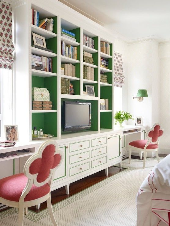 source: James Wagman Architect   Home office with built-in footed cabinets featuring emerald green backed cabinets with emerald green trim and brass hardware on cabinet door fronts. The built-in shelving is flanked by a pair of built-in desks lined with a pair of Suzanne Kasler Alexandra Side Chairs below the windows dressed with pink and green floral print roman blinds.