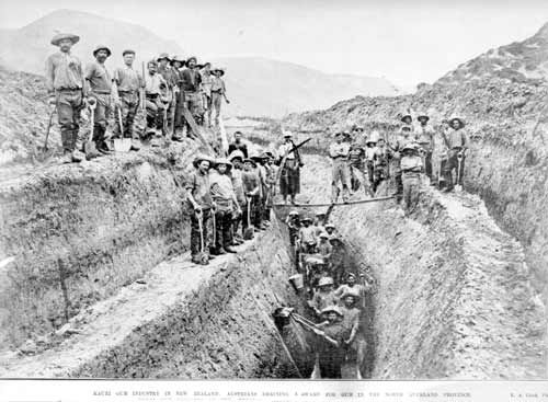 As the gumfields became depleted, the diggers turned to swamps for kauri gum. Digging 'on the face', this gang at Ōmāmari, north of Dargaville, is cutting a 10-metre-deep drain. Once a swamp was drained they would move in with spades and probes.