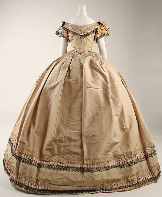 Back view of silk evening dress, British, ca 1860-64. Low body, shallow point; short double sleeve; bertha; box pleats and directional pleats in skirt. Trim is box pleated ruched ribbon between a blonde lace and a black lace; singular on bertha and sleeves, doubled on skirt. MET