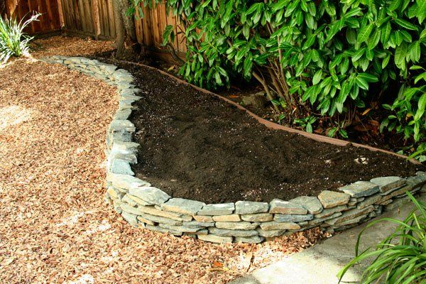 A freshly built dry-stack stone wall & raised bed ready for planting.
