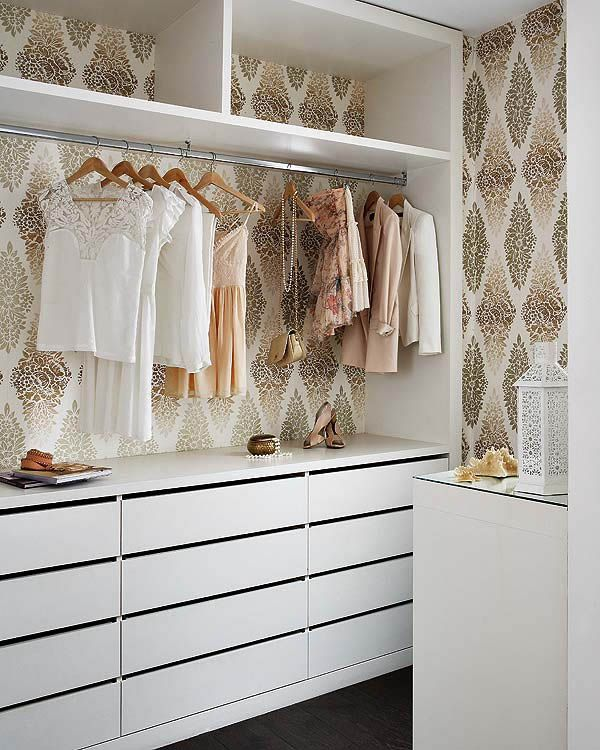 wallpapered closet with plenty of storage space