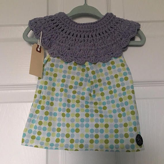 0-3 month size handmade baby girl dress with crochet top in slate cotton/nylon/polyester blend yarn with green & blue polka-dot pattern cotton fabric skirt, fastened at the back with a button. Lightweight and pulls over the head.