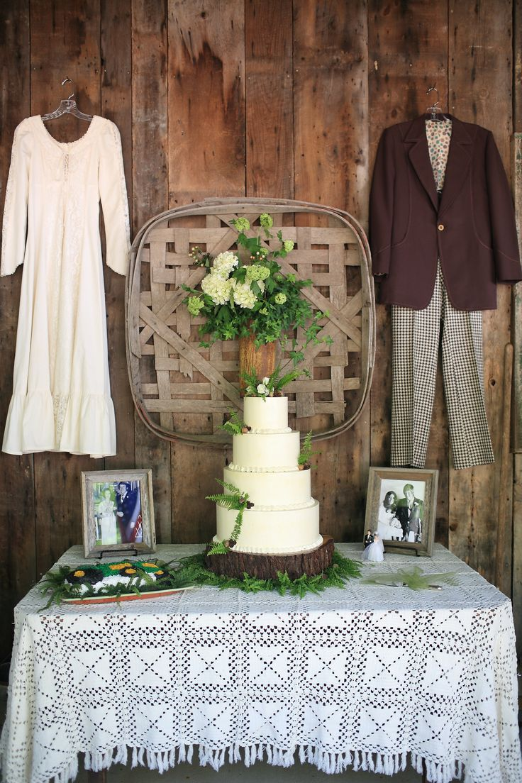 Fern Wedding in the Mountains: Vintage Cake table with parents' wedding clothes and parents' wedding pictures with fern themed wedding cake.