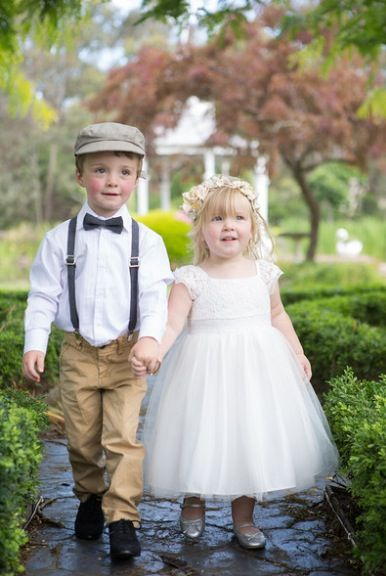 Vintage page boy with out the hat, black pants and the flower girl with yellow and white flower headpiece.
