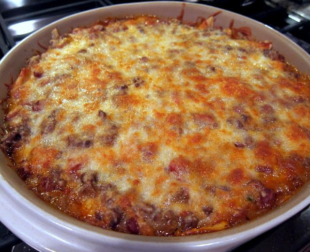 Mexican Casserole  1 pound lean ground beef  1 can Ranch Style beans  1 10-12 ounce bag tortilla chips, crushed (I didn't use the whole bag)  1 can Ro-tel tomatoes  1 small onion, chopped  2 cups shredded cheddar cheese, divided  1 package taco seasoning  1 can cream of chicken soup  1/2 cup water  sour cream and salsa for serving