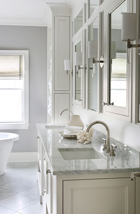 M bathroom features a white double washstand topped with carrera marble fitted with his and hers sinks and gooseneck faucets placed under framed inset medicine cabinets illuminated by nickel and glass wall sconces, Hudson Valley Lighting Wylie Wall Sconces.