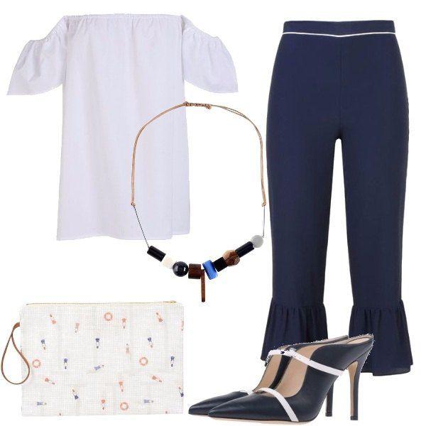 Pantaloni capri blu a vita alta, abbinati a top bianco che lascia scoperte le spalle, collana con applicazioni in metallo. Sabot con tacco a spillo e punta stretta, borsa a mano bianca con fantasia multicolor.