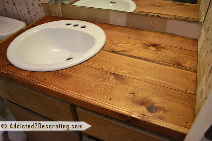 "Wood countertop in bathroom made with cedar fence pickets & plywood:  4 cedar fence pickets – $7.88 1″ x 2″ x 8′ cedar board – $2.46 2′ x 4′ x 3/4"" plywood – $15.65 Golden Oak stain – $4.78 Liquid Nails – $3.34 TOTAL -  $34.11"