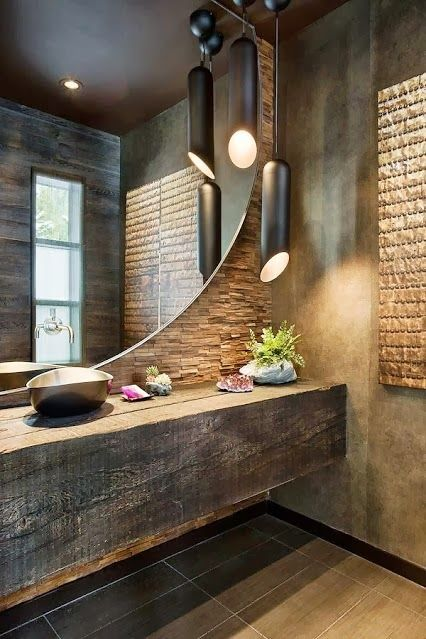 Textured wall with stacked stone veneer and a ginormous round mirror with metallic vessel sink - Stunning!