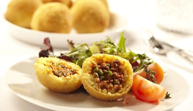Die frittierten Reisbällchen sind eine italienische Spezialität, gefüllt mit Erbsen, Hackfleisch und würzigem Parmesankäse. Die kräftige gelbe Farbe kommt vom Safran.