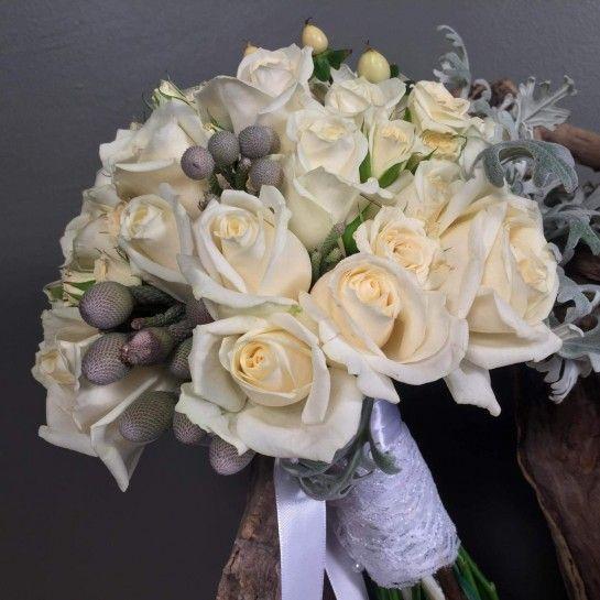 Νυφικό μπουκέτο (Ανθοδέσμη) γάμου από λευκά τριαντάφυλλα, λευκά μίνι τριαντάφυλλα, υπέρικουμ, silver brunia και dusty miller.Το δέσιμο είναι από δαντέλα και λευκή σατέν κορδέλα.Η πρόταση είναι ενδεικτική του NEDAshop.gr και μπορεί να τροποποιηθεί όπως εσείς θέλετε.http://nedashop.gr/gamos/nifikh-anthodesmh/leyka-triantafylla-yperikoym-dusty-miller-silver-brunia