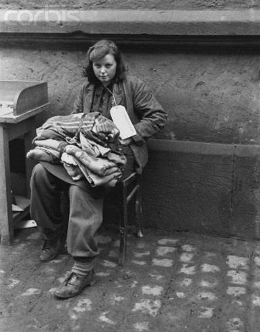 A 16 year old German girl with a bundle a 'Prisoner of War' label tied to her coat. She was captured, by Allied soldiers invading Germany, while trying to reach American (Allied) lines, and claims to have been a cook for the Hitler Jugend. 1945