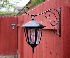 MUST DO! Dollar store solar lights on plant hook - LOVE this idea. Back yard