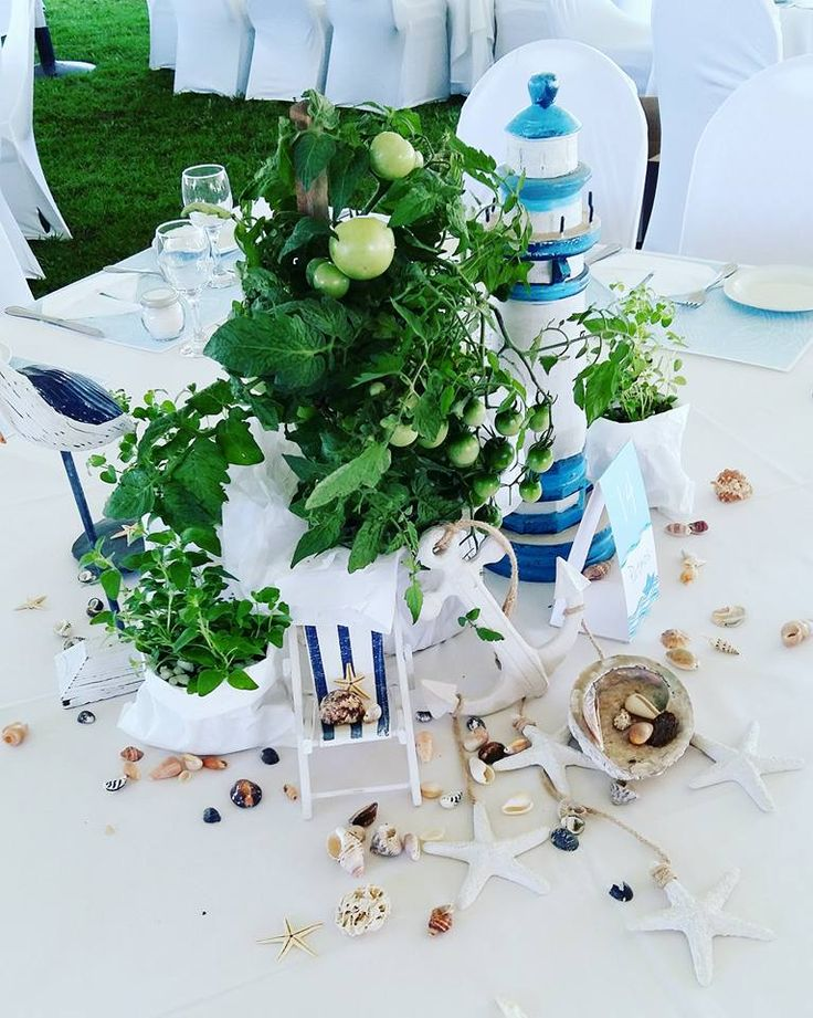 Centerpiece at our nautical themed christening with shells, a lighthouse sculpture, bird, and beach chairs.
