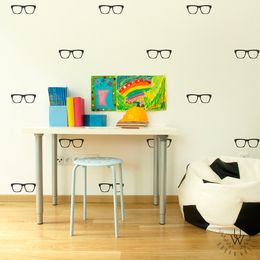 Small black glasses wall decals spaced equally on light beige wall behind a white desk with various school supply on top and a light blue stool. Beside the desk is a soccer ball beanie bag for sitting.