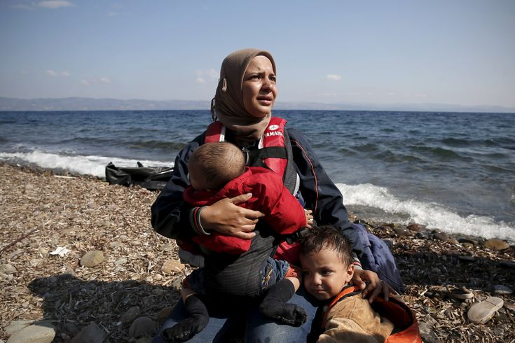 A Syrian woman cries while holding her children moments after arriving on a dinghy on the Greek island of Lesbos.