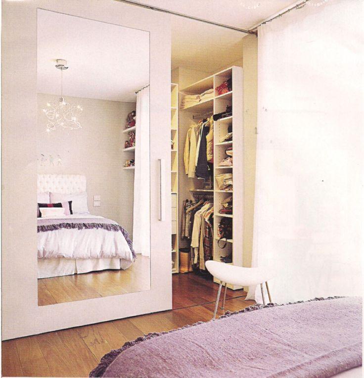Vestidor separado del dormitorio por medio de una puerta corrediza con un gran espejo que duplica el espacio