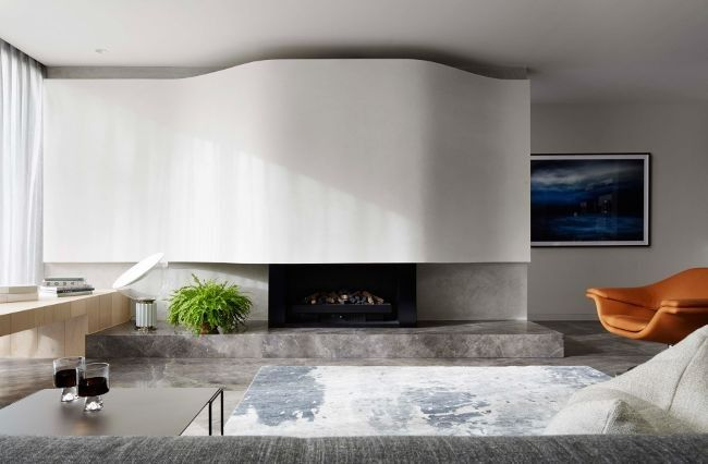 Fireplace inspiration from the Vogue Living archives: This room uses a sleek curved feature wall to draw attention to the modern fire place.