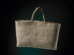 This is a kete, or woven basket, made in 1964 by Rangimāhora Reihana-Mete (1899-1993). It is woven from undyed kiekie (liana, a climbing forest plant) using the raranga (plaiting) technique, whereby strips of leaf are laid diagonally. A pair of haraheke (flax) handles are tied onto the interior. The kete is bleached, has a serrated top rim, and measures 18.5 cm x 30.5 cm.