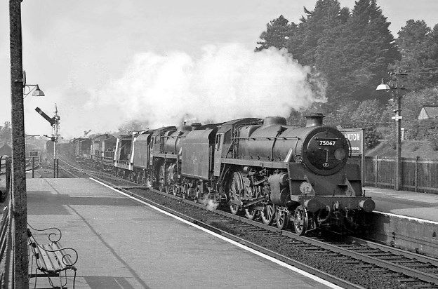 Two steam locos head-up a heavy Sunday engineering train through New Milton. The lead loco is a BR Standard Class 4 4-6-0, and the second is a BR Standard Class 4 2-6-0. Hampshire, England. Negative scan.