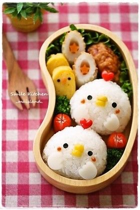 little chicken rice balls!  beak is corn, eyes seaweed (sushi nori).  i think white cheddar for hands when making in the us.  the top is just a heart toothpick.  maybe try ham?