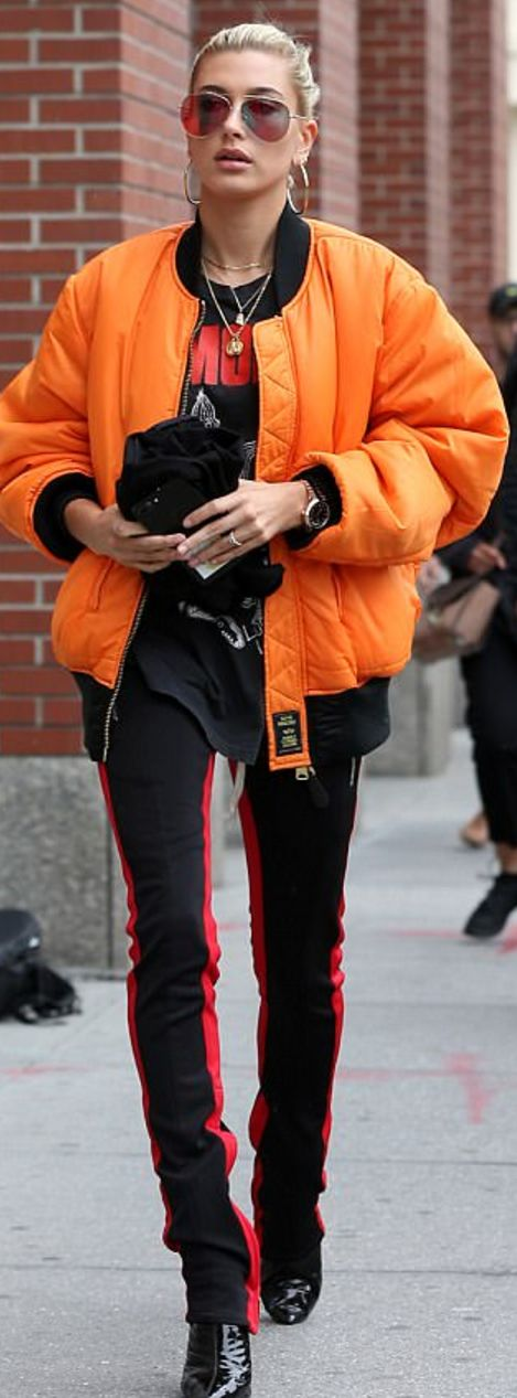 Who made Hailey Baldwin's black patent boots, stripe pants, and orange bomber jacket?