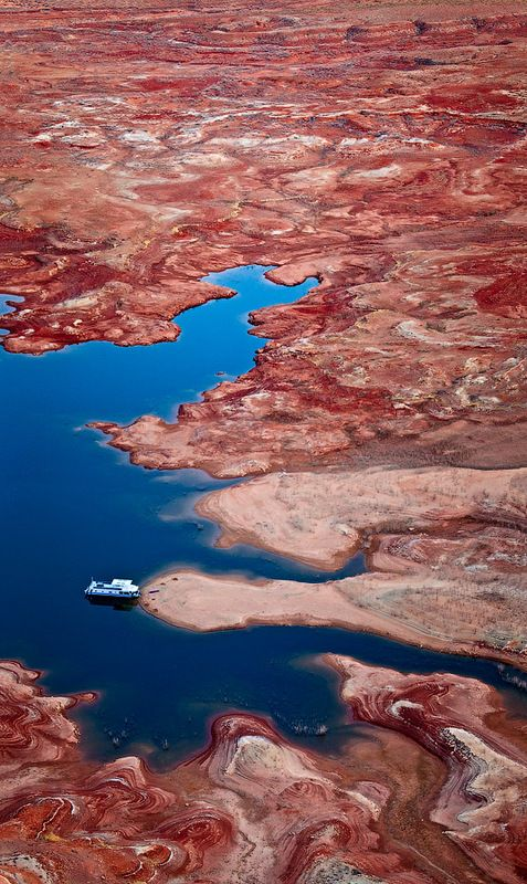 Lonely houseboat resting in the bay around Gunsite Butte. Lake Powell-Desert Jewel of Arizona