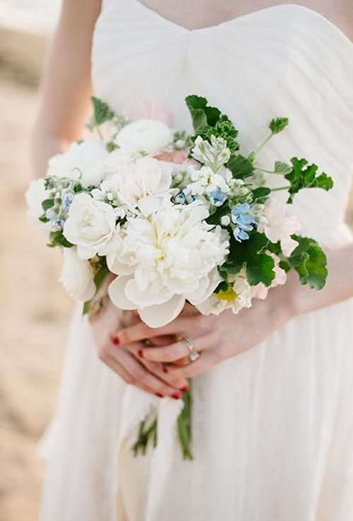 A crisp white bouquet includes ranunculuses, peonies, and anemones, with tweedia for a subtle pop of blue | Brides.com