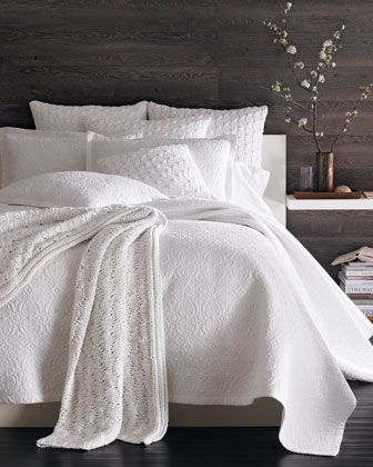 Dark stained wood accent wall with all white bed. Love all white!