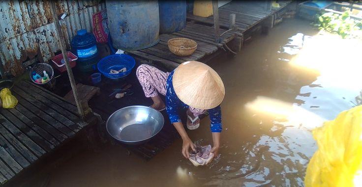 Een lokale vrouw wast een kip in het water, om deze vervolgens op te kunnen eten. Het leven van de vrouwen op de Mekong bestaat zeven dagen per week uit arbeid.