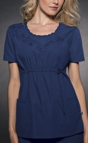 """Round Neck Top in Navy A round neck top features a floral embroidery with a delicate ruffle at front neck. An adjustable drawstring at side front waist, back darts, two curved patch pockets, and side vents complete this top. Center back length is 26 1/2"""".  Fabric: Brushed P/C w/Soil Release $26.99 #scrubs #nurses #doctors #medicaloutlet #studio #cherokee"""