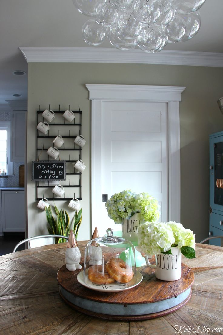 Love this farmhouse kitchen with modern bubble glass chandelier, farmhouse table and huge wall mounted bottle drying rack and using everyday items for an easy centerpiece like these adorable mugs and gnome salt and pepper shakers all from HomeGoods kellyelko.com sponsored pin