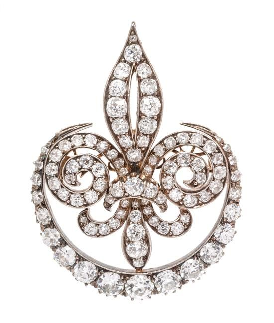 A Victorian Silver Topped Gold and Diamond Fleur De Lys Brooch, in an openwork design with scrolled detail, containing 11.28 carats of old European cut diamonds.