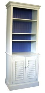 A lovely Bermuda styled bookcase with three adjustable shelves and two doors with wooden knobs. Choose from a solid color or a hand rubbed finish for an extra charge. Dimensions: 76H x 29.75W x 15.75D Crown Base Molding: 18D PHOTO • OPTIONAL Bermuda Shutter Doors • Victorian White over Bayside Exterior • Bayside Interior Backing Open panel door with dowel-Customer's own material. Bermuda and Basket weave doors have a 35door surcharge.