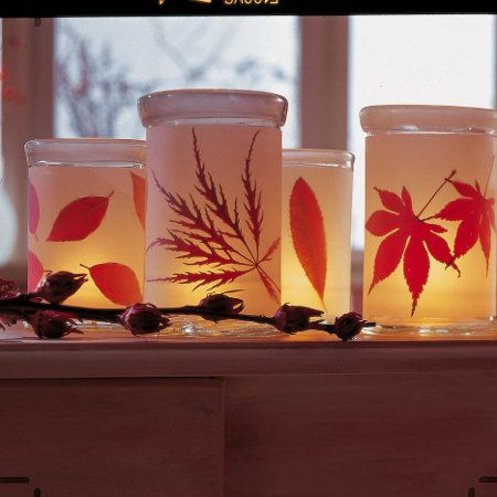 old glass containers wrapped in white paper that have various glued leaves= inviting laterns..