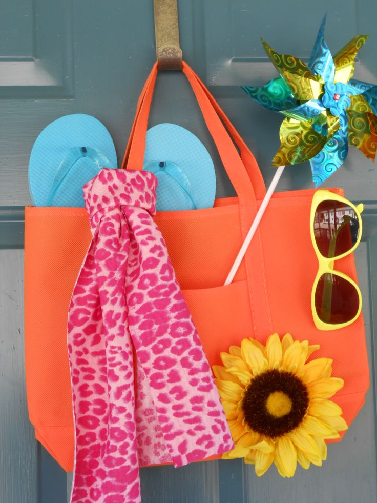 "Summer ""wreath"" for front door.  Everything came from the dollar store, a simple beach tote (kept folded flat), flip flops, scarf, sunflower, pinwheel and sunglasses.  Arrange as desired and hot glue parts in to place and you're done!"