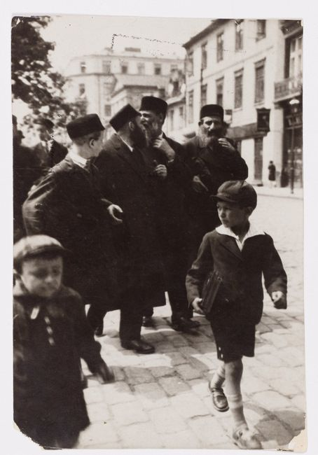 Warsaw. Hasidic men and boys walking along a city sidewalk on the way back from 'shul' (synagogue). A young non-Hasidic boy carries books under his arm.