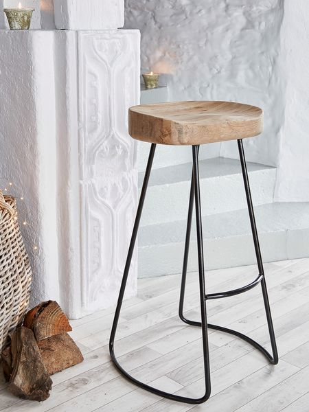 This weathered oak bar stool has a solid seat carved for comfort and elegant aged metal legs.