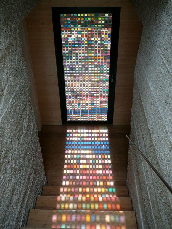 A porta, uma entre tantas criações inusitadas e detalhes incríveis que existem em sua casa, deu um ar incrível graças ao efeito visual conseguido com as cores da escala. Ao redor da moldura de madeira, dezenas de amostras quadradas de vidro colorido laminado, formam um grande mosaico que ao receber a luz natural do exterior criam a magia. Em cada pedacinho de vidro, uma anotação manuscrita dá nome à cor, mas usando como referência os elementos ao redor da casa.