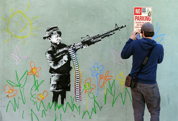 """A graffiti attributed to Banksy depicting a child wielding a machine gun, in black and white surrounded by colored flowers, is spotted in Westwood, California on Feb. 17, 2011. Another graffiti was ripped down Wednesday, Feb.16th in Hollywood, amid sightings of other pieces in a reported pre-Oscars publicity stunt. Banksy is nominated for best documentary for """"Exit Through the Gift Shop"""" at the Oscars, due to be announced on February 27th at the climax of Tinseltown's annual awards season."""