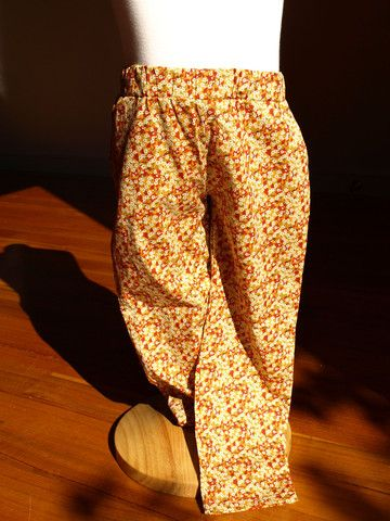 Tout Petit designed and made Liberty print Tana Lawn Fabric Mitsi Valeria Mustard coloured pants with little white & red floral print, elasticised waist, pockets and straight cut leg.  100% Tana Lawn cotton, made in Denmark.  Sizes 2, 4 and 6 $109.95