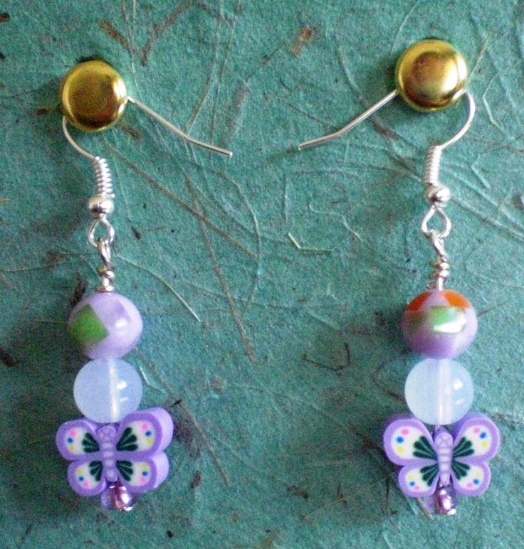 Orecchini pendenti con farfalle lilla in fimo, perle tonde in materiale sintetico che riprendono i colori nelle farfalle e monachelle argentata nichel free. (4,00)