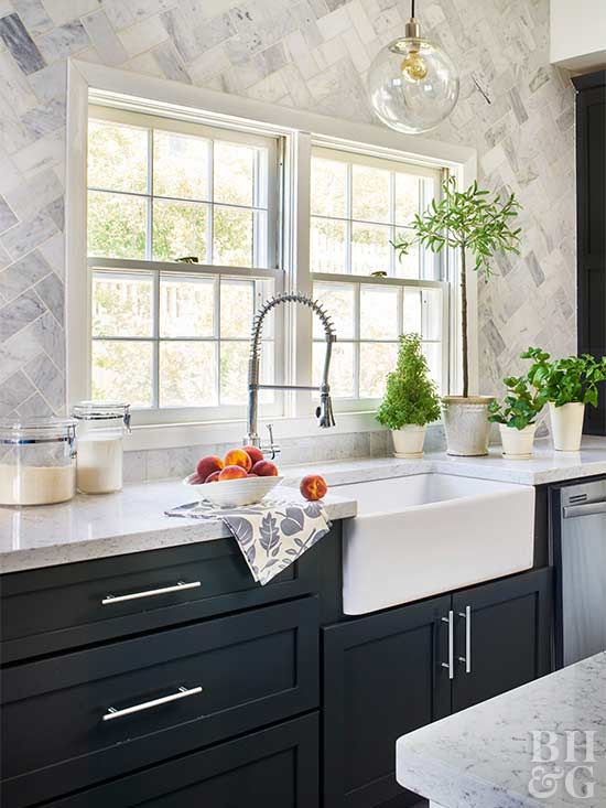 Removing upper cabinets from around the sink opened up the kitchen but left a visual void that begged to be artfully filled. By running marble tiles from countertop to ceiling, a subtle mosaic was born. Before the couple secured the pieces to the wall, they laid out the natural stone tiles on the floor in a herringbone pattern to get the right arrangement of light and dark tiles.