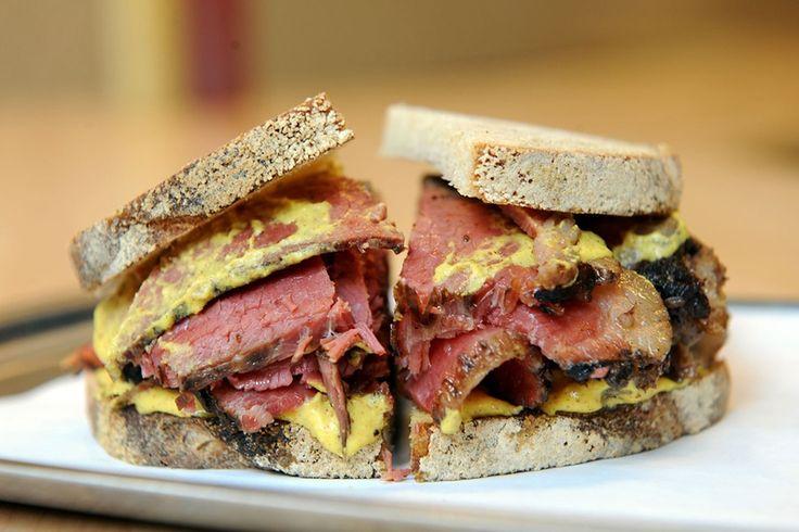 Montreal, Kanada - Smoked-Meat-Sandwich Die Kanadier lieben ihr herzhaftes Smoked-Meat-Sandwich, das dick mit geräuchertem Fleisch und Senf belegte Sauerteigbrot. Das Fleisch ähnelt dem Pastrami, hat aber eine stärkere Rauchnote und ist noch würziger.