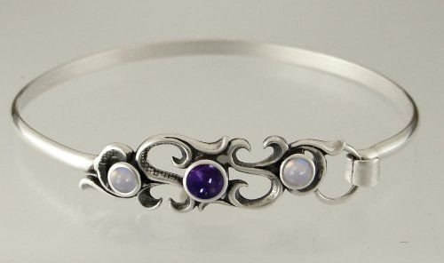 Sterling Silver Victorian Inspired Strap Bracelet with Genuine Iolite Accented with Rainbow Moonstone The Silver Dragon- Bracelets. $63.00. This Bracelet was Designed by The Silver Dragon, a Jewelry Shop in New England. Thank you for Supporting American Business.. Designed And Hand- Crafted in Sterling Silver. This Bracelet Fits a Standard Woman's Wrist. The Silver Dragon uses Sterling Silver that has been Reclaimed... Helping Save Mother Earth's Resources.. This Unique Bra...