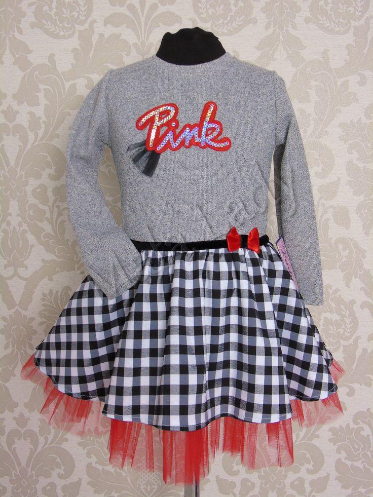 Sukienka Pink w czarno-białą kratkę z szenilu połączona z szarą dresówką bawełnianą. Dół kreacji wykonany z tiulu w kolorze czerwonym, odszytego podszewką. Sukienka przepasana z przodu czarnym paskiem w pasie z małą kokardą z boku. Sukienka posiada długie rękawy oraz kryty zamek z tyłu kreacji.Sukienka dostępna z dodatkami w kolorze różu lub czerni.