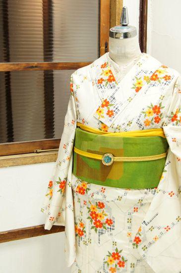 生成り色の地に、可憐な小花が形づくるモダンな幾何学模様と、西洋の花小窓を思わせるような六角形に重なるお花モチーフが織り出された正絹紬の袷着物です。
