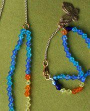 PSIQUE: Juego de pulsera y collar en cuentas multicolores, con dije de mariposa y cadena dorada.